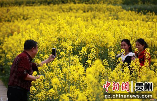2020年3月18日,游客在四川省毕节市黔西县洪水镇解放村赏花拍照。史开心 摄