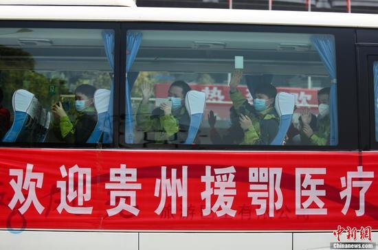 3月19日中午,贵州第七批支援湖北医疗队147名队员乘机从武汉返回贵阳。随后,医疗队员们乘坐大巴统一至指定地点进行集中隔离修养。图为大巴上的医疗队员挥手打招呼。 张晖 摄