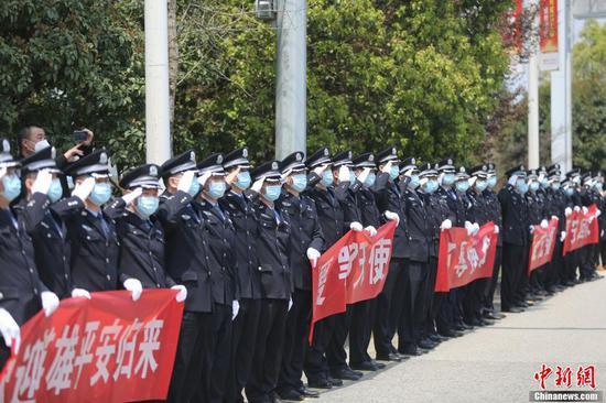 3月19日中午,贵州第七批支援湖北医疗队147名队员乘机从武汉返回贵阳。随后,医疗队员们乘坐大巴统一至指定地点进行集中隔离修养。图为民警向医务人员敬礼。 张晖 摄