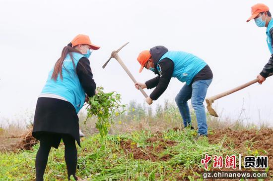 图为志愿者帮助老人春耕。