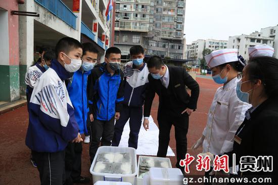 走读管理的贵州省凯里市第四中学九年级各班派四名学生错峰领取当地政府相关部门统一送的午餐。杨仁海 摄
