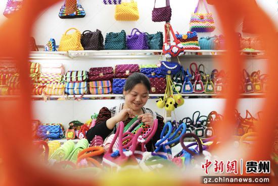"""贵州赤水市长期镇康桥社区,一名妇女在""""扶贫车间""""钩织产品。"""
