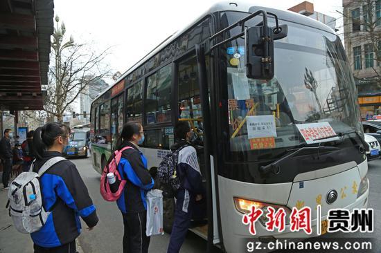 走读管理的贵州省凯里市第四中学九年级的学生在学校门口公交站台,其间保持1米的距离,排队上专线公交车。杨仁海 摄