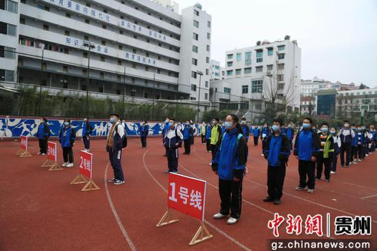 走读管理的贵州省凯里市第四中学九年级的学生,其间保持1米距离,列队候专线公交车送回家。杨仁海 摄