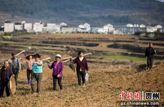 图为农民耕种完收工回家