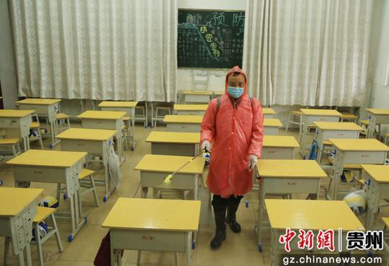 贵州省凯里市第四中学的一名教师对教室进行消毒杀菌。杨仁海 摄
