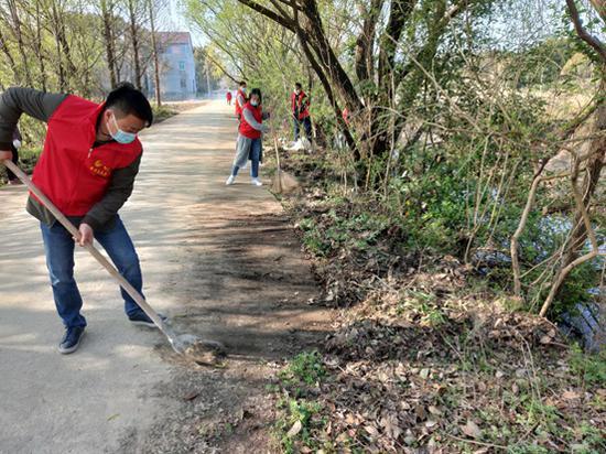 当地青年志愿者正在清理道路卫生死角 。陈梦娇 摄