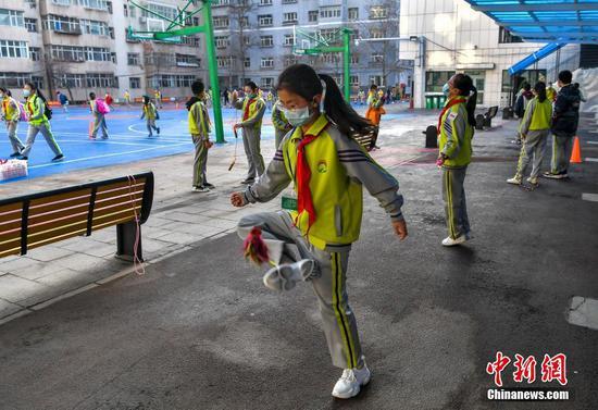 一名学生在校园踢毽子。中新社记者 刘新 摄