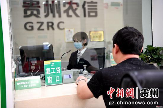 """3月23日,贵州省榕江农信社一网点,客户正在""""复工贷""""窗口办理业务。"""
