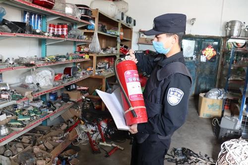民警正在检查灭火器是否过期。石晓坤 摄