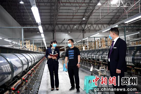 3月23日,贵州省榕江农信社工作人员在榕江县工业园区一家纺织企业里,了解企业复工复产情况。
