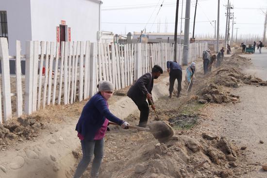 图为塔哈其镇古努恩布呼村各族群众正在清理渠道泥沙。列格金 摄
