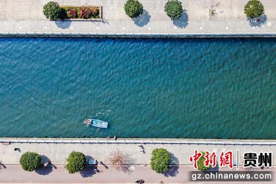 毕节市七星关城区河道管理处的工作人员正在倒天河打捞垃圾  陈曦 摄