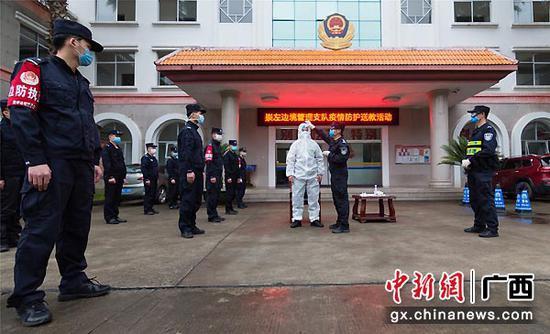图为教官团指导民警穿戴防护服。
