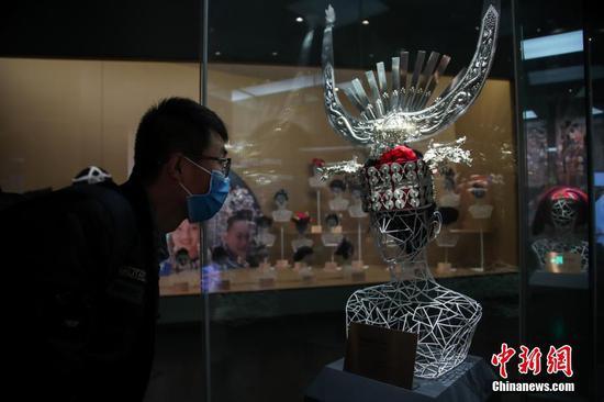 3月29日,一位男士戴口罩在貴州博物館民族服飾展廳內參觀。據悉,根據貴州省應對新冠肺炎疫情防控領導小組發布通告要求,貴州省博物館已于3月26日恢復開放。中新社記者 瞿宏倫 攝