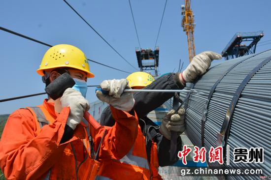 施工人员正在对主缆出现的夹丝进行调整。