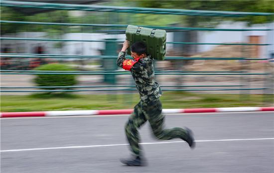 參賽官兵扛起40斤的彈藥箱進行沖刺。  胡港 攝