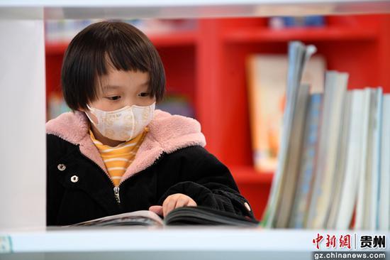 一名小读者正在贵阳市南明区图书馆内的少儿阅读区阅读儿童图书。赵松 摄