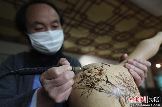 2020年4月21日,贵州省毕节市黔西县杜鹃街道岔白社区农民李德华的葫芦烙画展示厅,李德华加工葫芦烙画。