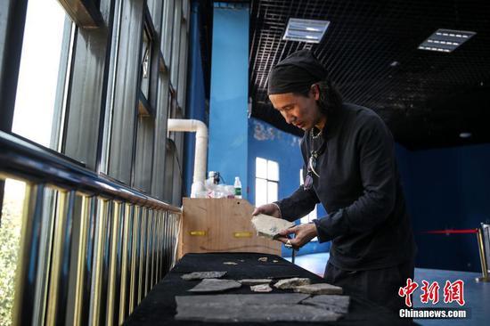 地质公园化石修复师李刚在整理化石。中新社记者 瞿宏伦 摄