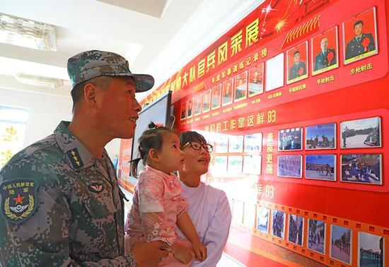 5月10日,王洁带着孩子认真观看丈夫孟令鑫取得的荣誉。罗兴仓 摄