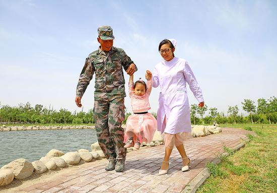 5月10日,一家三口悠闲的漫步在军营一角。罗兴仓 摄