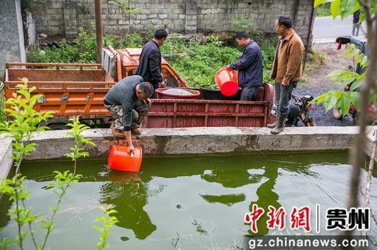 5月12日,在澳门金沙网上平台省毕节市大方县慕俄格古城街道凉井村,村民正在往车上装水。 罗大富 摄