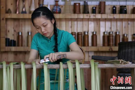 图为杨昌芹在为竹片刮青。 王长育 摄