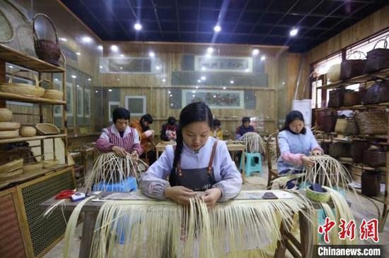 图为杨昌芹带领手工艺人们加紧编制竹工艺品。 王长育 摄