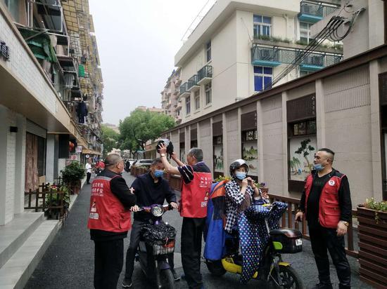志愿者正在帮助市民佩戴头盔。下城区委宣传部