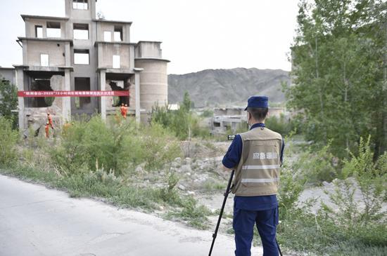 图为消防救援人员使用拍摄模拟地震画面用5g传回指挥车。