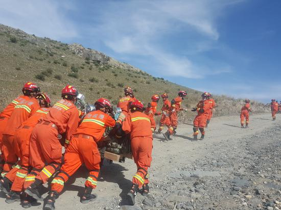 """图为新疆阿勒泰消防救援人员正在徒步挺进模拟演练""""震中""""。"""