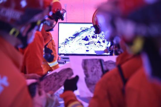 图为消防救援人员通过5g传回的视频查看模拟地震的现场情况。
