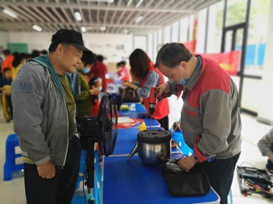 志愿者给居民修理电器 环渚街道提供