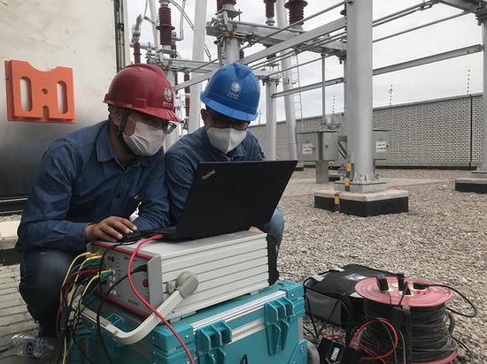 电科院技术人员张路和送变电公司技术人员在750千伏博州变开展智能站保护装置二次回路完整性测试技术现场验证(王利超摄)