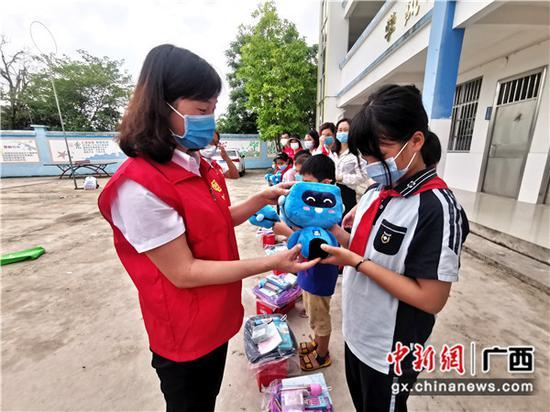 志愿者为孩子们送上可爱的蓝宝。关喆琳      摄