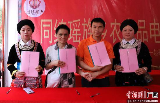 盘鲜菊(左一)和同练电商签订购销合同 。 覃美 摄