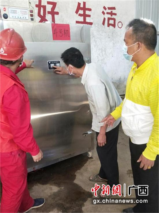 南方电网广西崇左市公司工作人员和拾义村村干部查看茶叶加工设备。许乐兴 摄