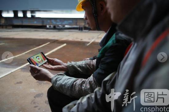 5月21日,大发棋牌玩法贵州 贵阳,一处建筑工地上的施工人员通过手机直播观看开幕会。当日,全国政协十三届三次会议在大发棋牌玩法北京 人民大会堂开幕。 中新社记者 瞿宏伦 摄