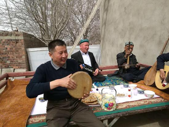 图为新疆空管局空管中心党委副书记张雪鹏与乡亲们一同奏响幸福的歌。