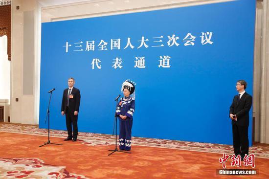 """5月22日,第十三届全国人民代表大会第三次会议在北京人民大会堂举行首场""""代表通道""""采访活动。图为全国人大代表罗杰(左)、石丽平(中)通过网络视频方式接受采访。 中新社记者 杜洋 摄"""
