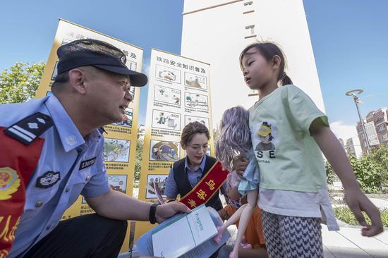 民警在社区采取答题有奖的方式向小朋友宣讲铁路安全常识。李国贤 摄