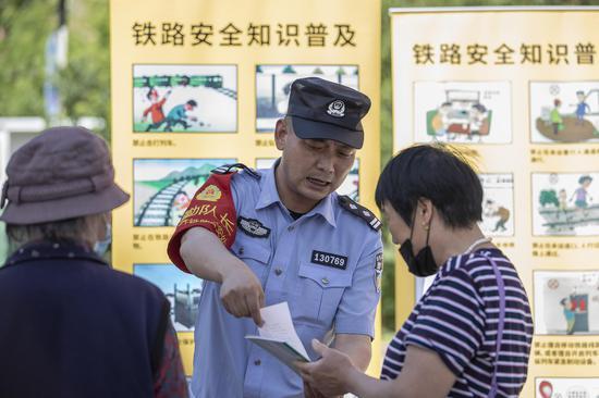 """民警向社区大妈们详细讲解""""发现报告铁路安全隐患""""的奖励办法。李国贤 摄"""