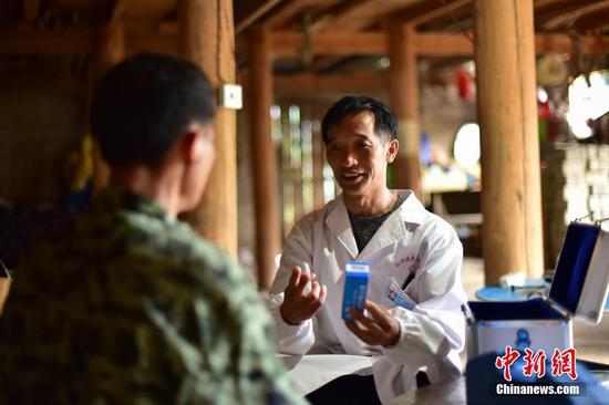 龍光慶(右)向村民楊勝良介紹藥品服用的注意事項。 楊武魁 攝