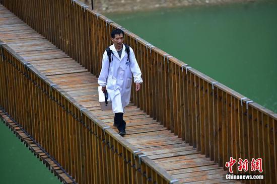 出診返程途中,龍光慶行走在河道鐵索橋上。 楊武魁 攝