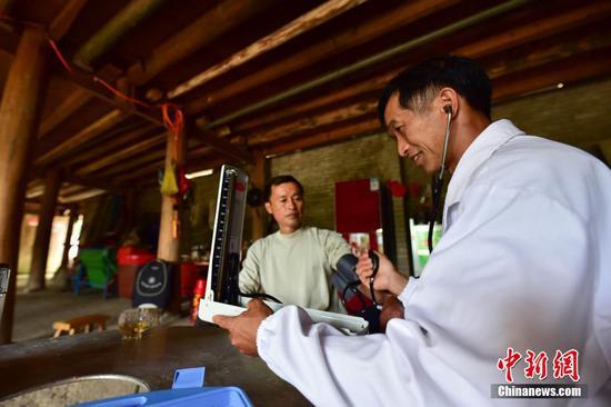 龍光慶(右)為村民楊勝良測量血壓。 楊武魁 攝