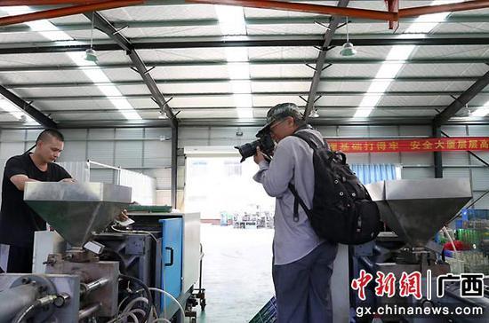 图为摄影家用镜头记录仿真花扶贫车间。何光民  摄