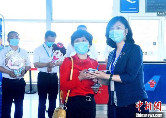 南航新疆分公司党委书记王曼(右一)为购买了此次航班首张机票的乘客杨素梅赠送纪念品。 张思维 摄