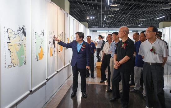 寒石向参观展览的领导嘉宾等介绍作品。  王刚 摄