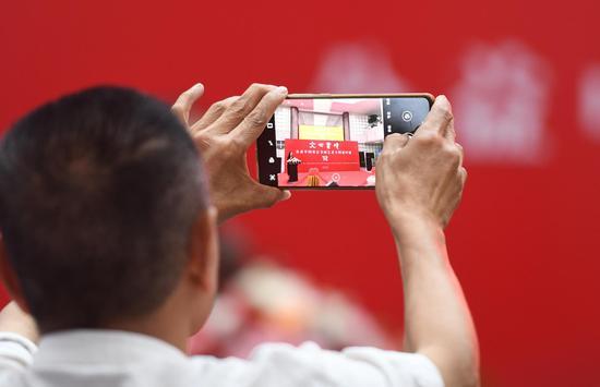 参加活动者在开幕式现场拍照。  王刚 摄